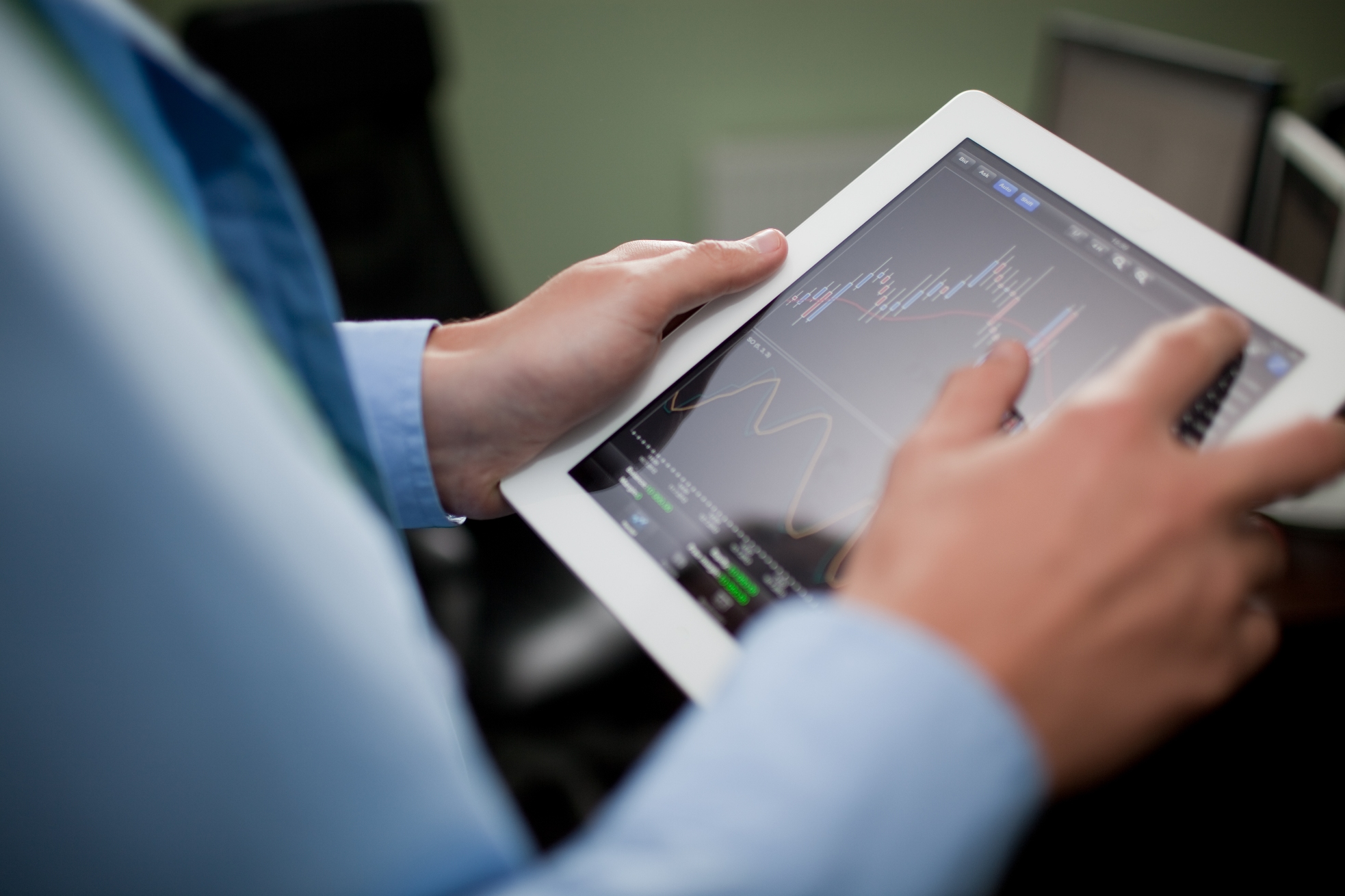 Professional viewing stock information on tablet.